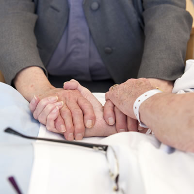 A female patient in a hospital bed holding hands with the hospital chaplain