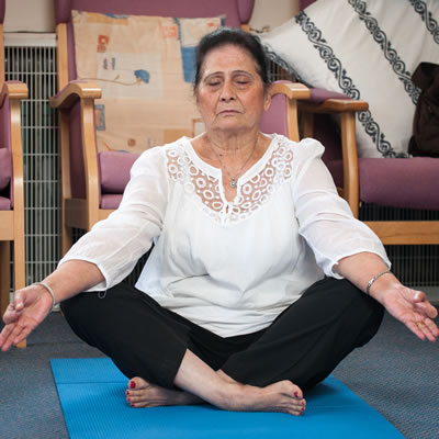 A woman sitting on the floor, with her legs crossed, meditating