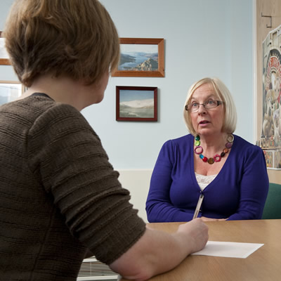Description: A mature woman patient consulting a GP in the surgery consulting room.